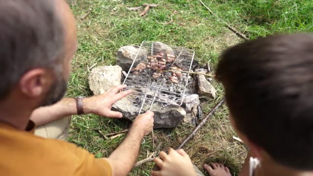 mann bereitet grill über offenem lagerfeuer mit sohn vor - picknick stock-videos und b-roll-filmmaterial
