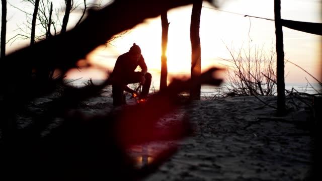 ビーチキャンプでたき火を準備する男 - 孤独点の映像素材/bロール