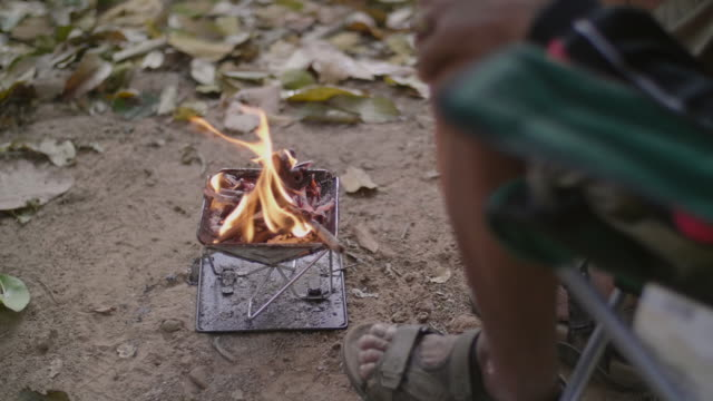 man preparing bonfire on a camp in the forest. - holiday camp stock videos & royalty-free footage