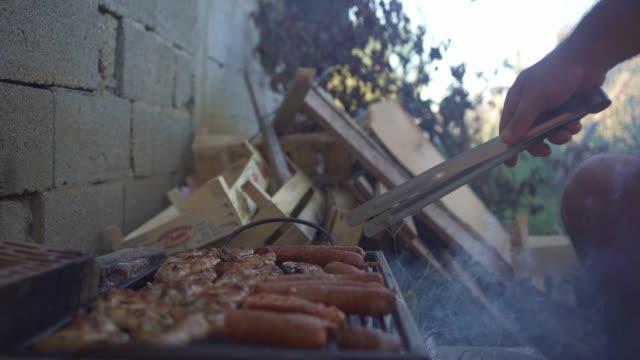 裏庭で屋外で鶏肉とソーセージバーベキューを準備する男 - コイントス点の映像素材/bロール