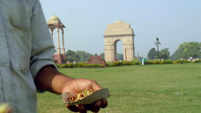 cu, man preparing chole bhature, close-up of hands, india gate in background, new delhi, india - 戦争記念碑点の映像素材/bロール