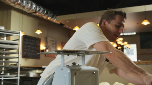 man preparing dough in a commercial kitchen - brot backen stock-videos und b-roll-filmmaterial