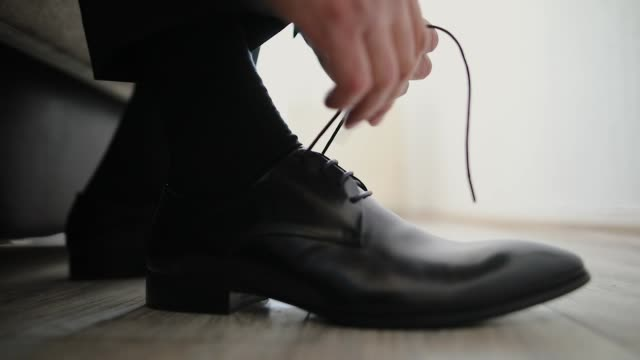 man preparing for a wedding day, tying shoe laces close-up - footwear stock videos & royalty-free footage