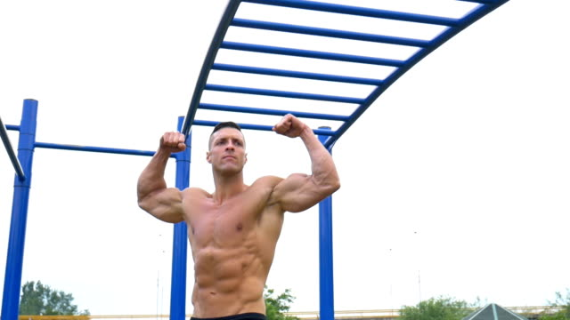 man preparing for workout in the local park - flexing muscles stock videos & royalty-free footage