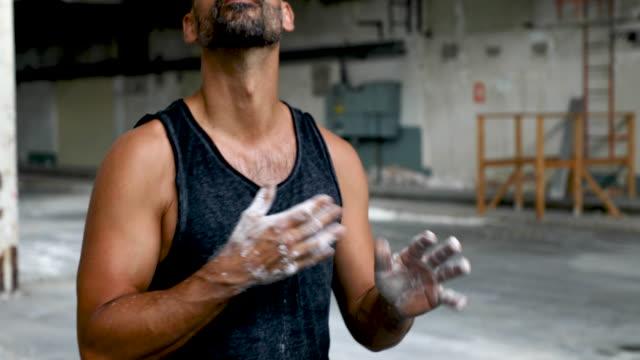 vídeos de stock, filmes e b-roll de homem preparando-se para treino com anéis de ginástica - giz equipamento esportivo