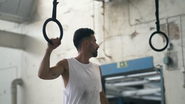 放棄された倉庫で体操リングを準備する男 - 電話を切る点の映像素材/bロール