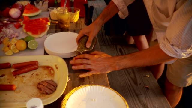 vídeos de stock e filmes b-roll de cu tu td man preparing hot dog at party / brooklyn, new york - hot dog