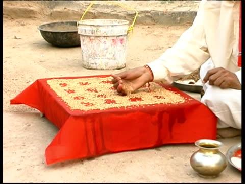 vidéos et rushes de ms man preparing rice for fuja ceremony, rajasthan, india - coiffe traditionnelle