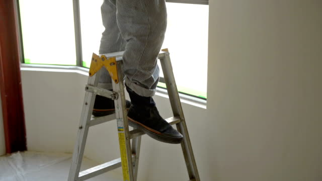 man preparing to paint by taping window - step ladder stock videos & royalty-free footage