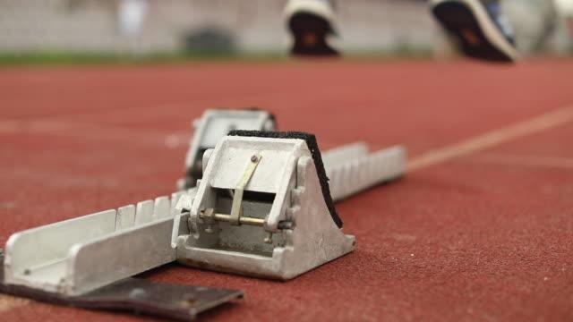 男 100 m ダッシュを実行する準備をして - スターティングブロック点の映像素材/bロール