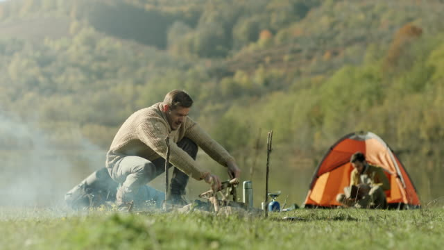 man preparing wood for campfire while his friend book reading by the tent - firewood stock videos and b-roll footage
