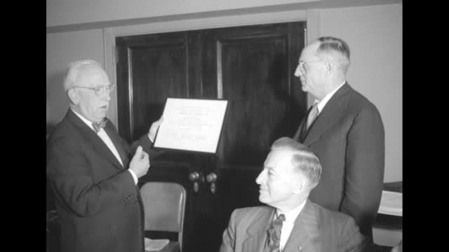 man presenting another man with plaque at 15th anniversary dinner of teaching film custodians / the men shake hands and the honoree returns to his... - plakette stock-videos und b-roll-filmmaterial