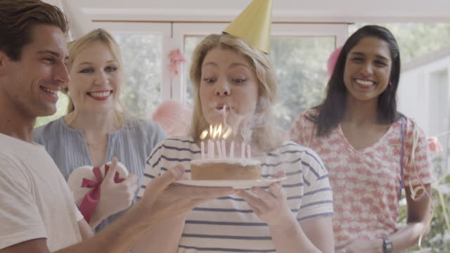 man presents a birthday cake to woman, she blows out candles while friends are cheering. - birthday gift stock videos & royalty-free footage