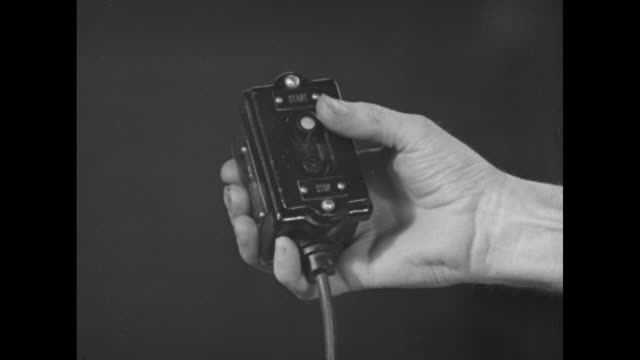 man presses a small on and off switch of a 'remote control' / note: exact year not known - bedienungsknopf stock-videos und b-roll-filmmaterial