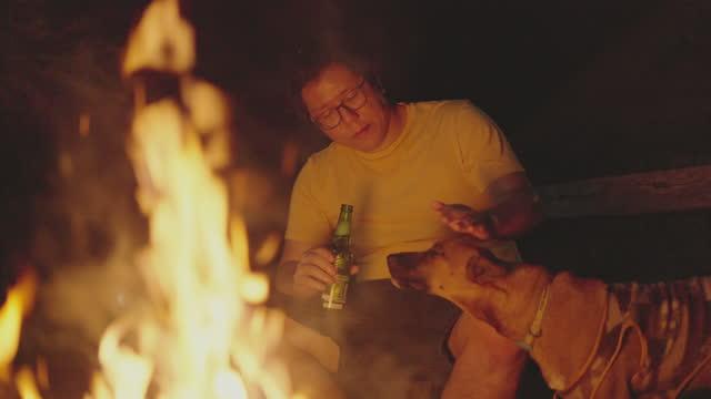 slomoの男は、キャンプファイヤーの前で犬にビールを提供するふりをします - 外乗点の映像素材/bロール
