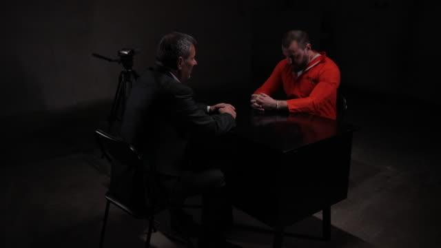 man prisoner in interrogation room with lawyer - prisoner orange stock videos & royalty-free footage