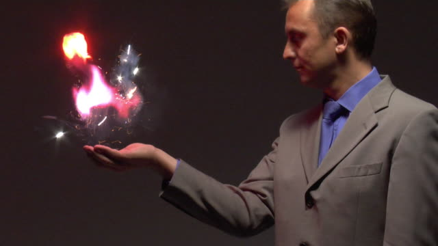 ms man produces explosion from hand, side view - 手品点の映像素材/bロール
