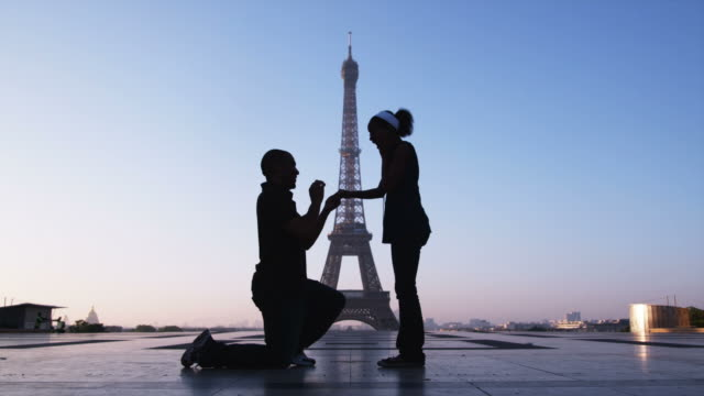 man proposing marriage to woman in front of the eiffel tower - ひざまずく点の映像素材/bロール