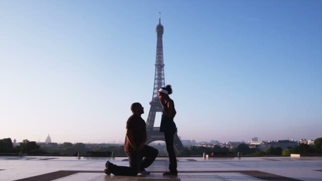 man proposing marriage to woman in front of the eiffel tower - coniugi video stock e b–roll