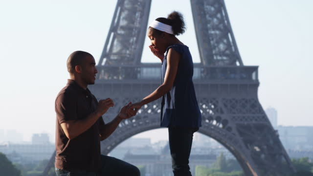 man proposing marriage to woman in front of the eiffel tower - fidanzata video stock e b–roll