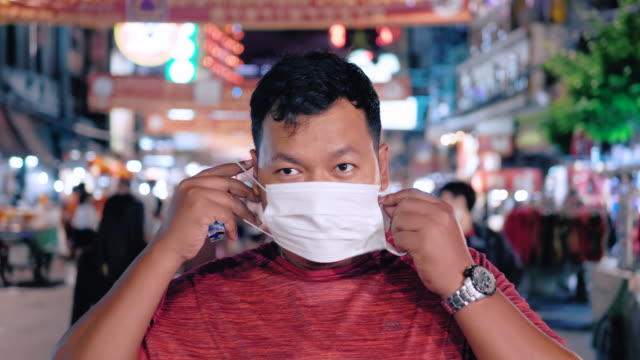 man protect yourself from the china coronavirus with masks at chinatown in thailand. - coronavirus stock videos & royalty-free footage