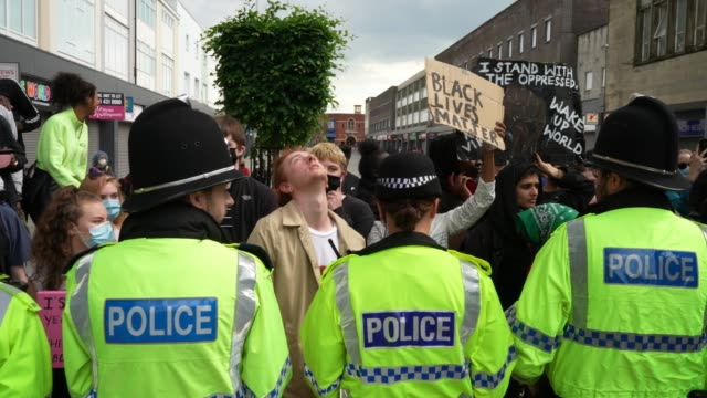 a man protests behind the police forming a line during an antiracism demonstration on june 13 2020 in bolton england a number of antiracism... - rassismus stock-videos und b-roll-filmmaterial