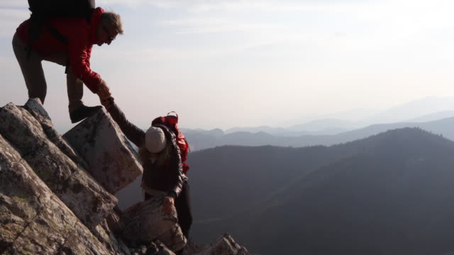 man provides assistance to female companion on pinnacle summit - due persone video stock e b–roll