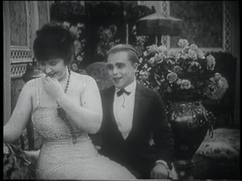 B/W 1916 man puckering lips at woman, she starts to kiss him but turns away embarrassed (jump cut)
