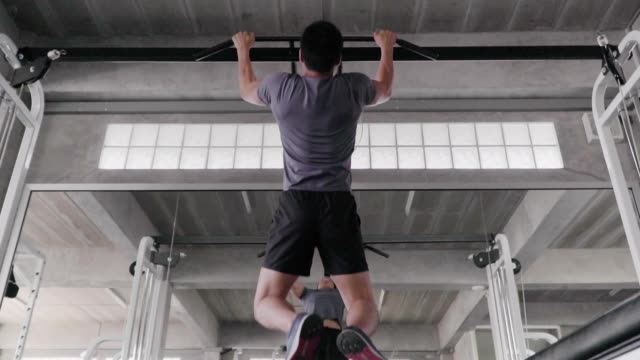 (slow motion) man pull up and looking himself in mirror at fitness gym. - chin ups stock videos and b-roll footage