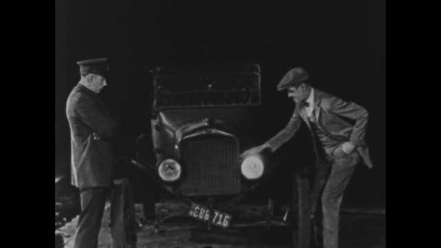 vídeos de stock, filmes e b-roll de 1925 man pulled over by police officer attempts to fix broken headlight by touching alternate lights until he and police officer simultaneously hit both headlights off the car - feito pelo homem