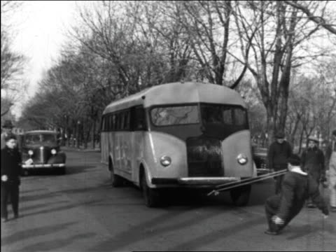 vidéos et rushes de b/w 1949 man (charles bayerjon) pulling bus by rope in mouth / quebec, canada / series - 1949