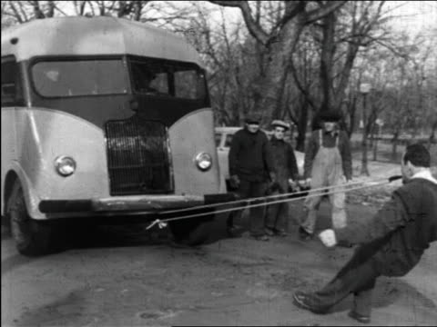 b/w 1949 pan man (charles bayerjon) pulling bus by rope in mouth / quebec, canada / series - 1949 stock-videos und b-roll-filmmaterial