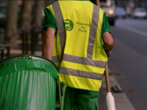 rear view man pulling garbage can + broom on side of street with traffic / paris, france - trash can stock videos and b-roll footage