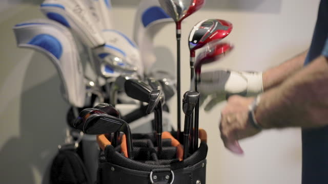 man pulling golf club from bag - golf club stock videos & royalty-free footage