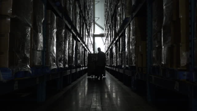 Man pulling hand held pallet truck in aisle of warehouse
