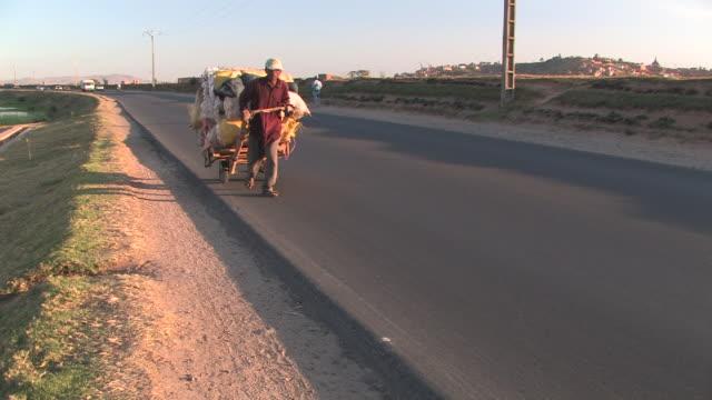 ms, man pulling loaded cart down paved road, antananarivo, toamasina province, madagascar - pulling stock videos & royalty-free footage