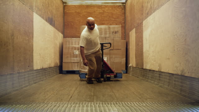 man pulling stock on hand operated pallet truck - hubwagen stock-videos und b-roll-filmmaterial
