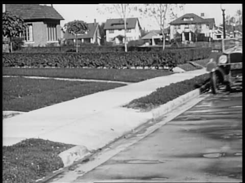 b/w 1928 man pulling up to curb in vauxhall convertible / industrial - 1928 stock videos & royalty-free footage