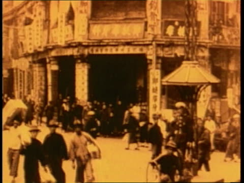 a man pulls a rickshaw on a busy street in china - 1910 stock-videos und b-roll-filmmaterial