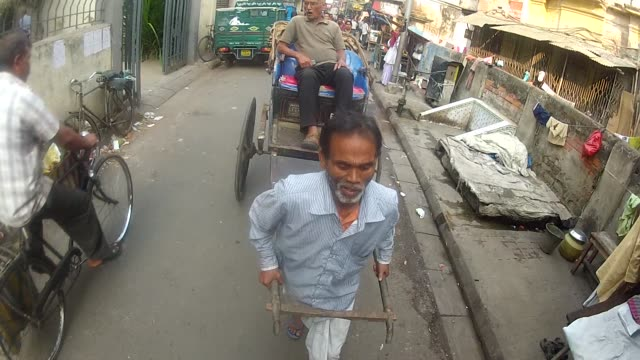 a man pulls a rickshaw through a narrow street in india. - rickshaw stock videos and b-roll footage