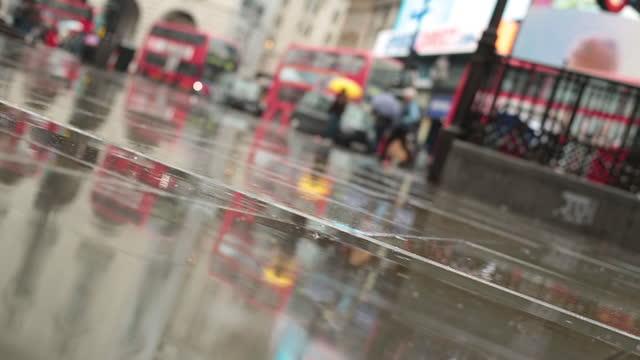 vídeos y material grabado en eventos de stock de a man pulls a rolling suitcase across a rainy london sidewalk with double decker buses passing in the background. - vista inclinada