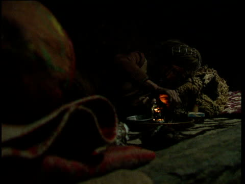 vídeos de stock, filmes e b-roll de man pulls on opium pipe inside squalid shack as small chickens roam afghanistan - abuso de substâncias