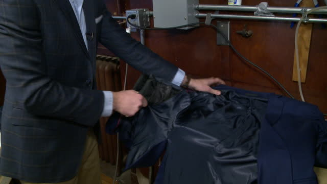 wgn man pulls out bulletproof padding from men's suit lining at aspetto inc store in frederiscksburg virginia on february 7 2018 - sportschützer stock-videos und b-roll-filmmaterial