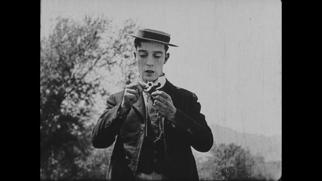 1922 man (buster keaton) pulls petals off of a daisy, mouthing 'she loves me, she loves me not' - buster keaton stock videos and b-roll footage