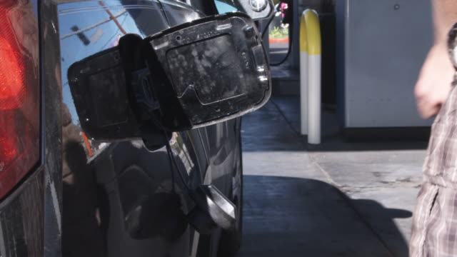 vidéos et rushes de a man pumping gas, focus on hand - faire le plein d'essence