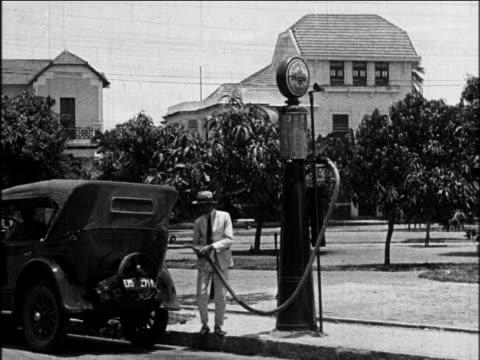 b/w 1927 man pumping gas into back of gm car / industrial - ölindustrie stock-videos und b-roll-filmmaterial