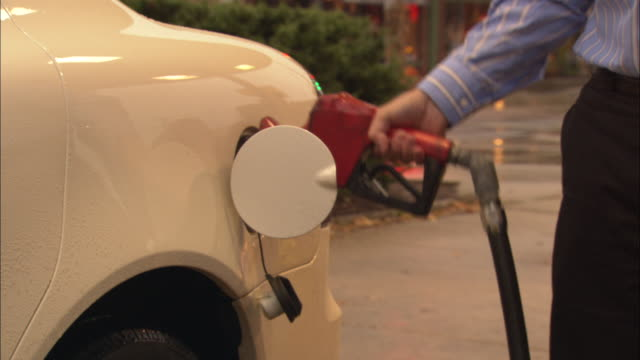 a man pumps gas at the gas station. - tankstelle stock-videos und b-roll-filmmaterial