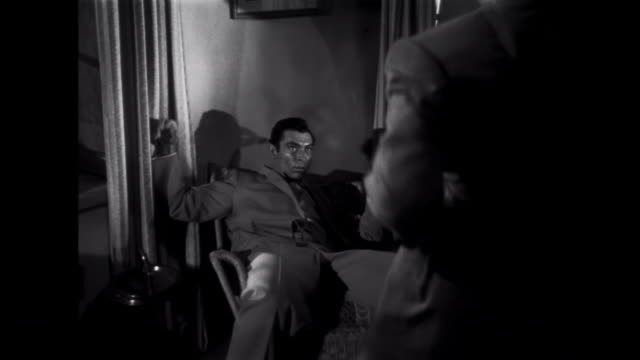 1952 A man punches and throws a gangster into a chair