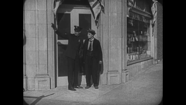 1921 Man (Buster Keaton), pursued by two angry police officers, hides behind a third