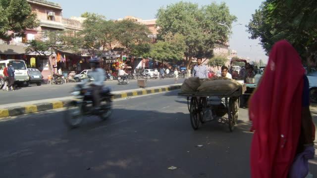 Man push cart full of nuts past camera